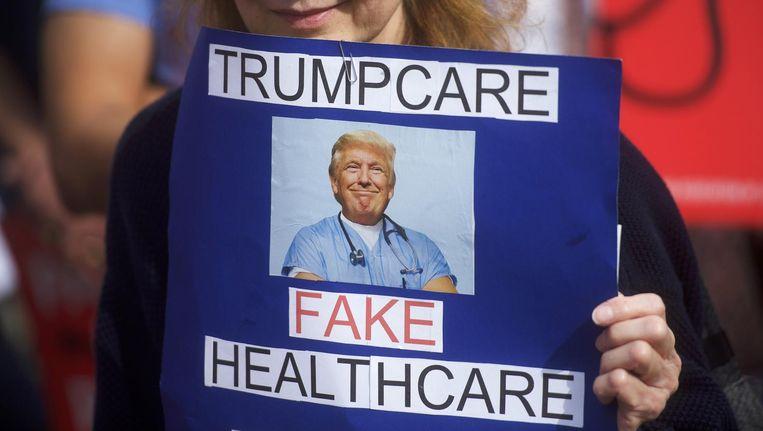 Een demonstrant houdt een bordje omhoog met 'Trumpcare is nepzorg' op een bijeenkomst eerder dit jaar. Beeld afp