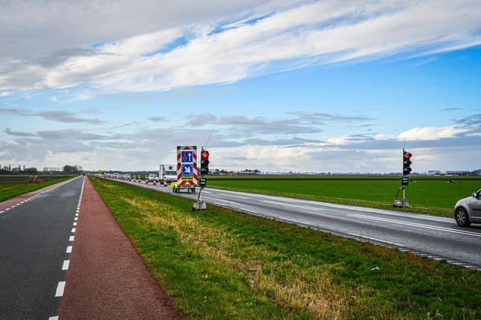 Met tijdelijke verkeerslichten wordt het verkeer op de Hanzeweg om en om langs het loslatende asfalt geleid.