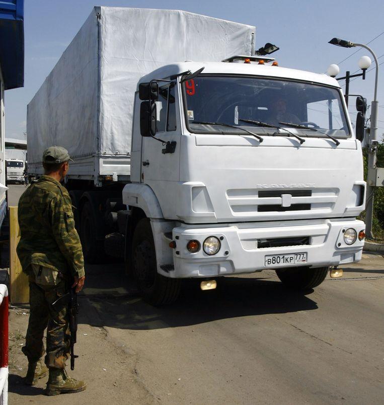 Een Pro-Russische separatist laat een deel van het Russische hulpkonvooi de grens over. Beeld afp