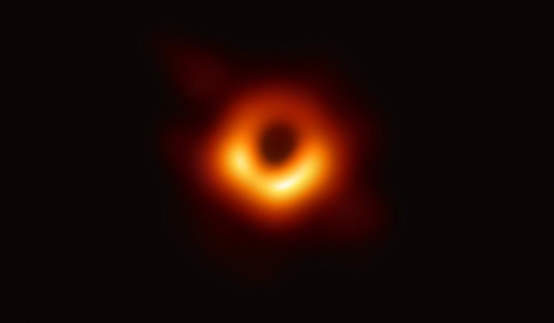 De eerste foto van een zwart gat, in het centrum van het verre sterrenstelsel M87 (afstand: 500 triljoen kilometer). Je ziet hier een ring van licht, afkomstig van áchter het gat. Doordat zijn waanzinnige massa - het zwarte gat is zo'n 6,5 miljard maal zwaarder dan de zon - aan dat licht trekt, buigt hij het om zich heen, tot een vurige cirkel. Omdat uit een zwart gat geen licht ontsnapt, kun je zijn binnenste niet zien. De zwarte vlek op de foto onthult wel de contouren van zijn waarnemingshorizon, het 'point of no return' waar voorbij je niet meer aan het zwarte gat kunt ontsnappen. In werkelijkheid is de lichtring op de foto zo'n 100 miljard kilometer breed.