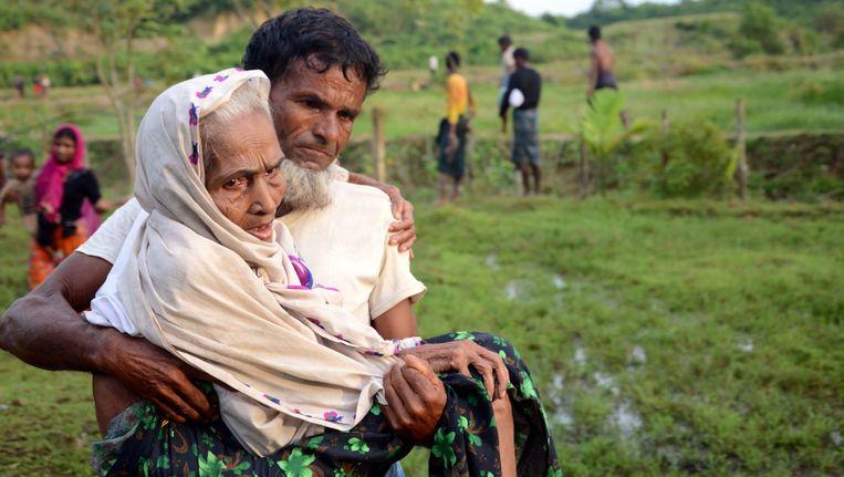 Rohingya draagt zijn moeder over de grens tussen Myanmar en Bangladesh. Beeld afp