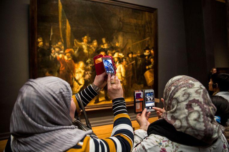 Bezoekers van het Rijksmuseum in Amsterdam maken foto's van de collectie, die een overzicht biedt van de Nederlandse kunst en geschiedenis met onder andere werken van 17de-eeuwse Nederlandse meesters als Rembrandt, Vermeer en Hals. Beeld Hollandse Hoogte / Arie Kievit