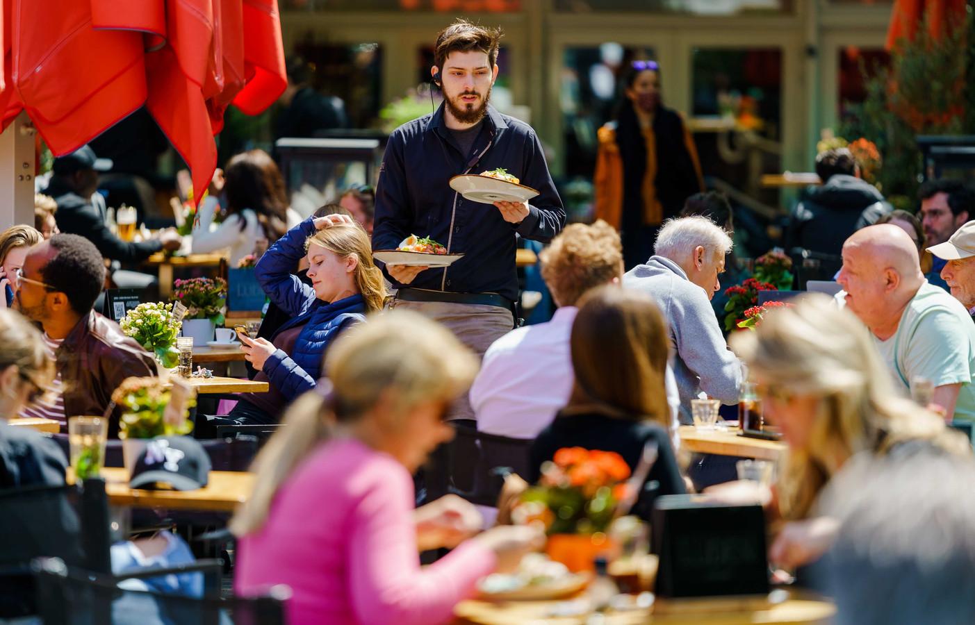 Foto ter illustratie. Een ober werkt op een terras in het centrum van Den Haag.