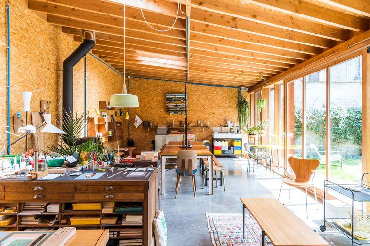 In het atelier staan vintage schatten zoals het metalen gele tafeltje met stoelen achteraan rechts van Mathieu Matégot,  lampen van Pierre Guariche en wandplanken van Marcel Gascoi. Beeld Luc Roymans
