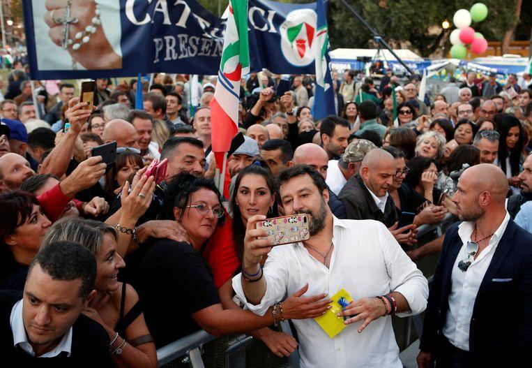 Lega-partijleider Matteo Salvini neemt een selfie met supporters na de manifestatie in Rome op 19 oktober. Beeld REUTERS