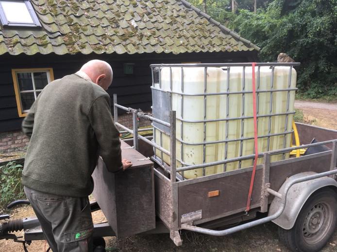 Boswachter Theo Putmans van het Brabants Landschap vult de kubus met een kuub water, zodat ze jonge aanplant van water kunnen voorzien.
