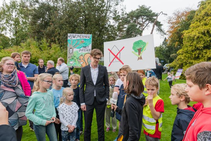 Wethouder Dolf Smolenaers (D66) legt aan kinderen van het Rembrandplein uit waarom hier huizen moeten komen.