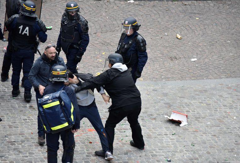 Op de beelden is te zien hoe Benalla (hier rechts) een betoger hardhandig aanpakt.  Beeld AFP