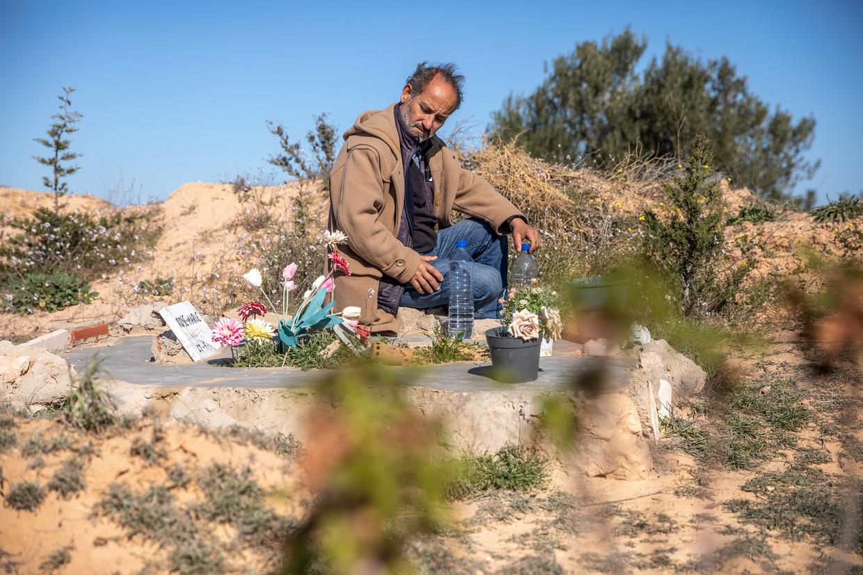 Chamseddine Marzoug zit bij een van de ruim vierhonderd graven voor verdronken migranten in Zarzis. Beeld Sven Torfinn / de Volkskrant