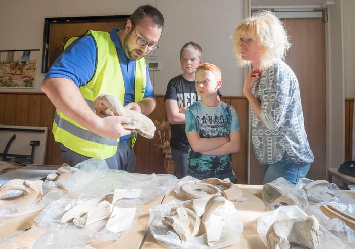 Joost van den Berg van SCEZ laat een stuk kruik zien aan de neven Thijs en Sil (de jonge archeoloog in spe staat vooraan) en moeder Natasja uit Hansweert.