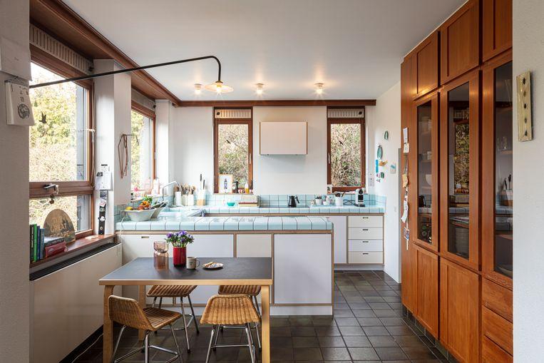 De compacte keuken met werkblad van blauwe tegeltjes is een project van Studio Helder.   Beeld Tim Van de Velde