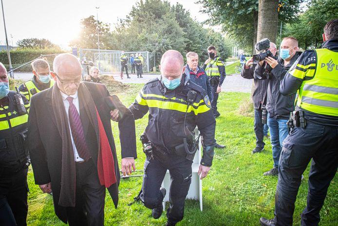 Actievoerder Martin Mourik wordt door de politie meegenomen en afgevoerd.