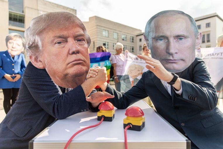 Activisten met maskers van de Amerikaanse president Trump en de Russische president Poetin meten hun krachten terwijl ze hun handen boven een symbolische knop houden om hun respectievelijke kernbommen te doen afgaan. Archiefbeeld.