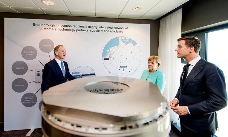 ASML in betere tijden. Bondskanselier Angela Merkel en minister-president Mark Rutte bezoeken chipmachinefabrikant ASML. Beeld Robin van Lonkhuijsen