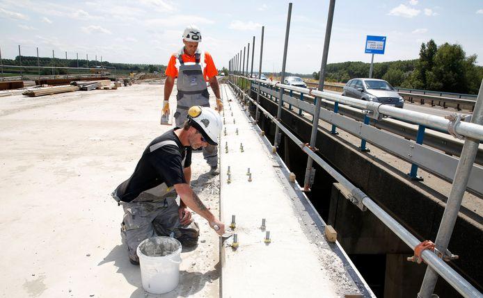 Bert (zittend) en Wil werken het nieuwe viaduct aan de Axelse Sassing af, terwijl het verkeer over het oude viaduct door kan rijden