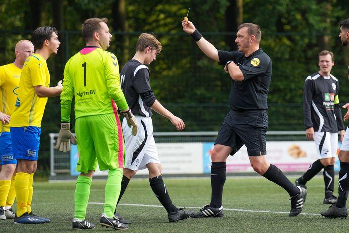 Scheidsrechter Henk Peters trekt de gele kaart voor Hannes Poppinghaus van SC Veluwezoom, in het duel tegen SC Westervoort.