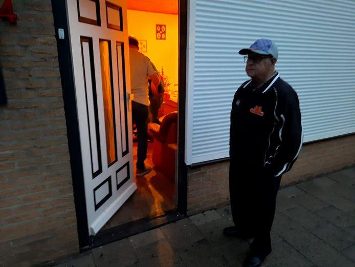 Toon Verhees staat voor zijn ondergelopen huis, terwijl binnen de boel wordt schoongemaakt.
