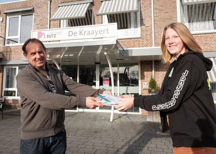 Wil de Rond, leidinggevende van De  Kraayert, neemt een stapel kaarten in ontvangst van Madelief van Ham.
