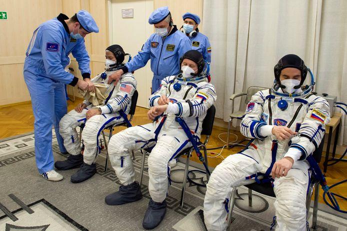 L-R: NASA-astronaut Mark Vande Hei, Russische kosmonaut Oleg Novitski and Russische kosmonaut Pyotr Doebrov tijdens een pakkentest in Bajkoenoer voor hun lancering naar het ISS.