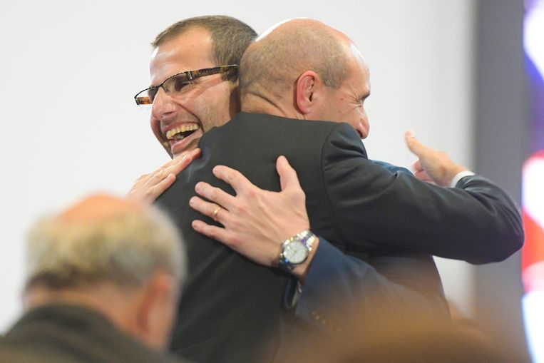 Robert Abela (links) wordt door zijn tegenstrever Chris Fearne omhelsd. Beeld AFP