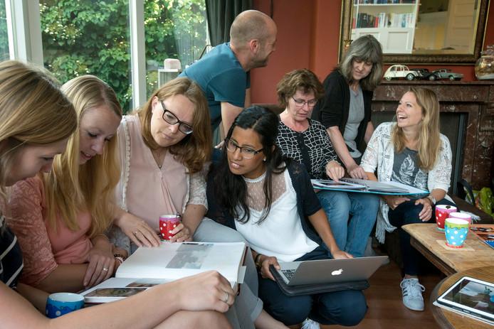 Docenten basisschool Arnhorst bekijken in dit stakingsuurtje bij een van hen thuis elkaars vakantiefoto's.