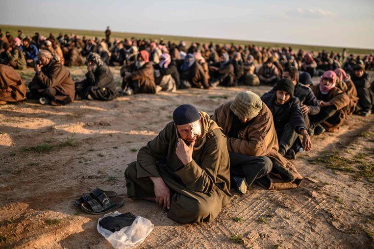 Mannen die ervan verdacht worden IS-strijder te zijn, wachten op hun ondervraging door Syrische strijdkrachten. Beeld AFP