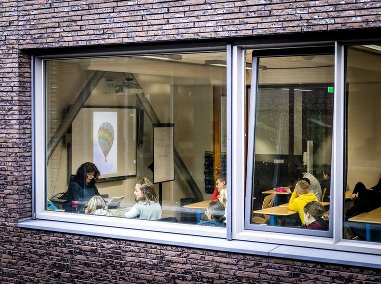 Een klaslokaal van een school in Haarlem waar een raam is opengezet voor de ventilatie.  Beeld ANP