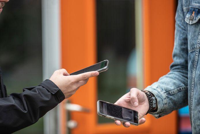 Beveiliger controleert een coronabewijs voor het betreden van een horecagelegenheid.