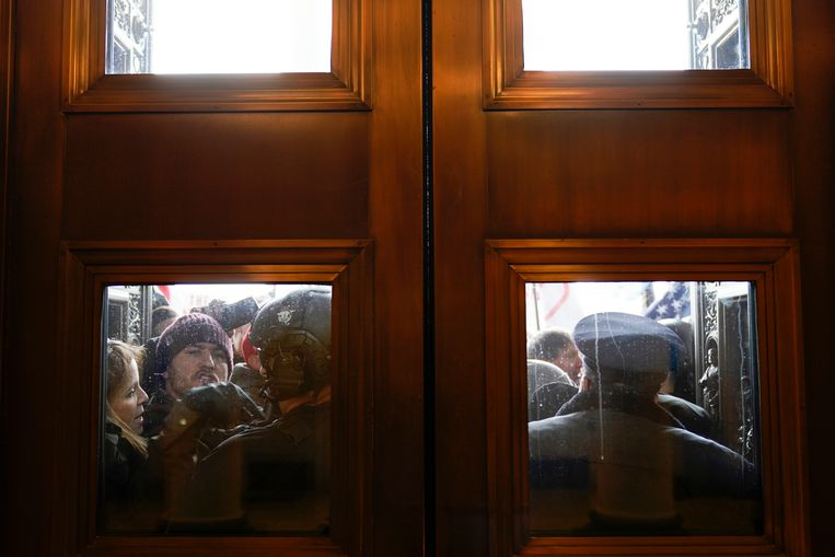 Demonstranten staan tot tegen de deuren aan de oostelijke ingang van het Huis van Afgevaardigden. Beeld AP