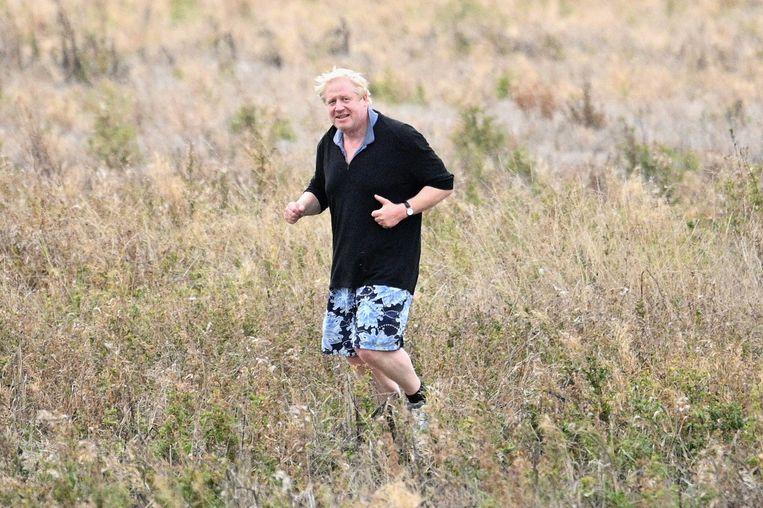 Boris Johnson rent door een veld tijdens zijn ochtendrondje voorafgaand aan het partijcongres op dinsdag. Beeld Getty