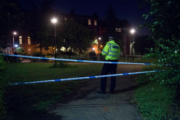 Een politieagent op de plaats waar begin juni een 17-jarige jongen werd doodgestoken. Twee tieners werden opgepakt. Beeld Photo News
