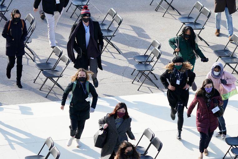 Mensen maken zich uit de voeten voor het Capitool in Washington – maar angstig zijn ze niet. Dit is een evacuatie-oefening tijdens de repetitie van de inauguratie, morgen, van Joe Biden als de nieuwe president van de Verenigde Staten.  Beeld AP