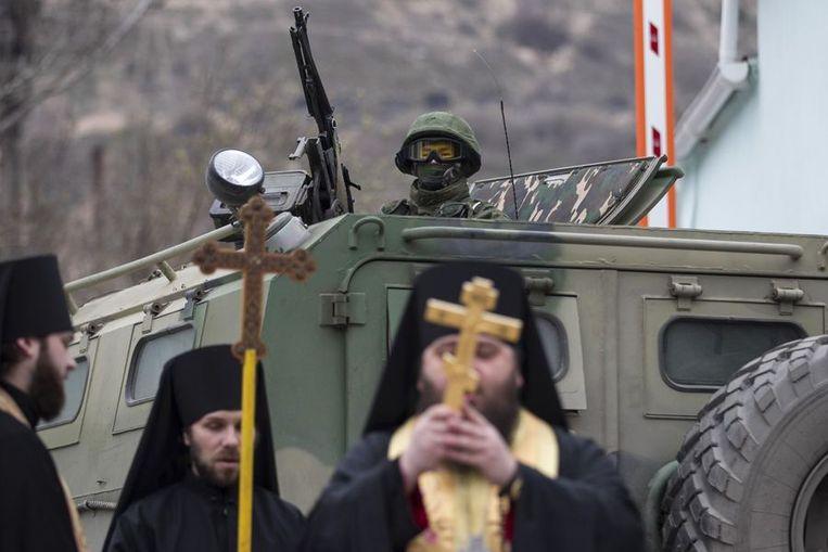 Orthodoxe monniken bidden bij een Russisch legervoertuig in Balaclava op de Krim. Beeld reuters