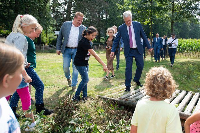 Deltacommissaris Peter Glas krijgt op het 'groenblauwe' schoolplein bij basisschool Pax Christi in Overdinkel door leerlingen aangewezen waar een kikker zit.