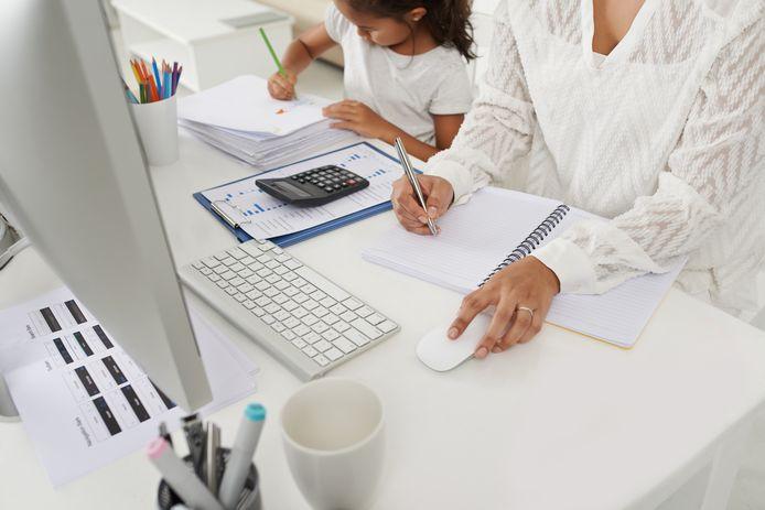 Een vrouw werkt van thuis uit, terwijl haar dochtertje naast haar een tekening maakt.