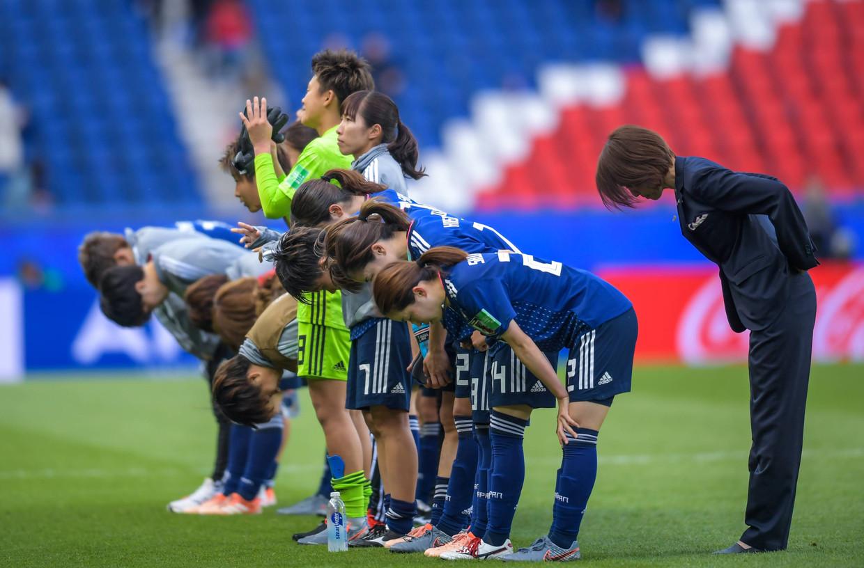 De speelster van Japan en coach Asako Takakura (rechts) buigen het hoofd na de groepswedstrijd tegen Argentinië. Beeld BSR