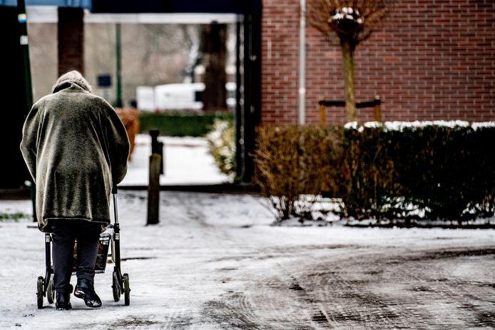 Bejaarde vrouw achter de rollator.
