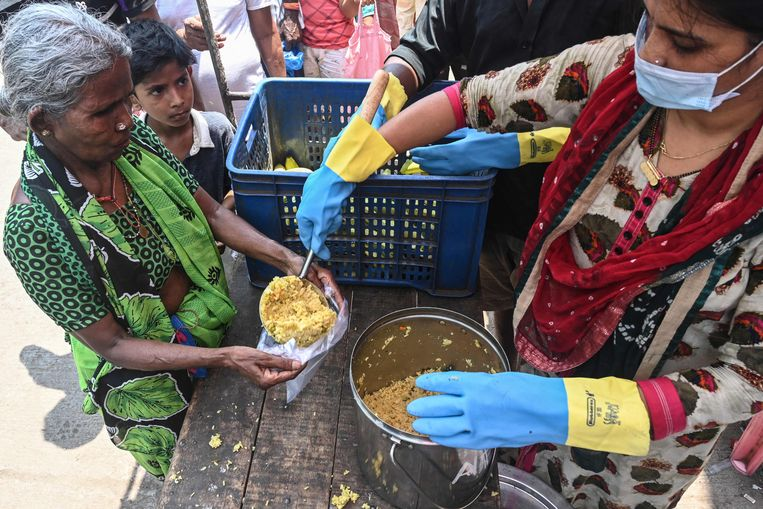 Een maatschappelijk organisatie in Mumbai in India verstrekt in april voedsel aan behoeftigen.  Beeld AFP