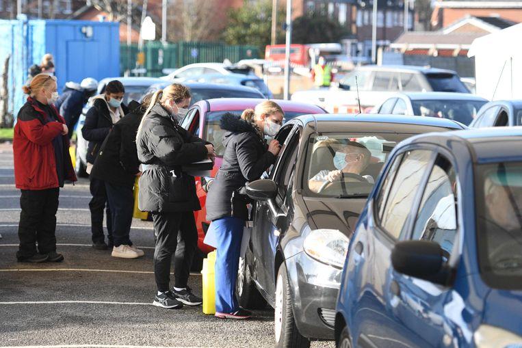 Tachtigplussers ontvangen het vaccin van Pfizer in de drive-in in Hyde, in de buurt van Manchester. In het Verenigd Koninkrijk zijn de vaccinaties al begonnen. Beeld AFP