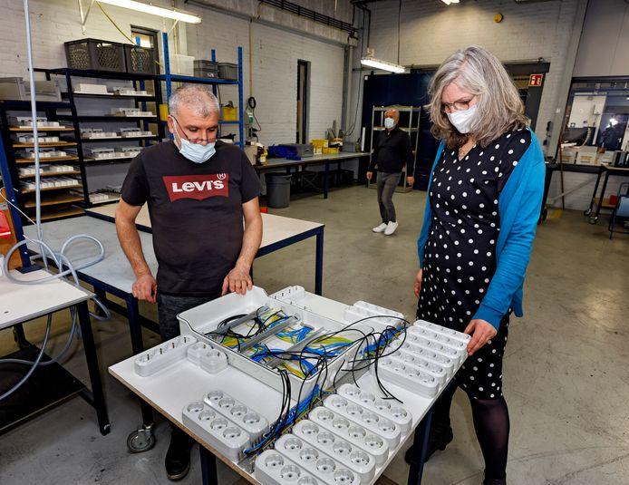 Nicole van der Wekken krijgt van een medewerker op de sociale werkplaats uitleg over de stekkerdozen die er worden gemaakt.