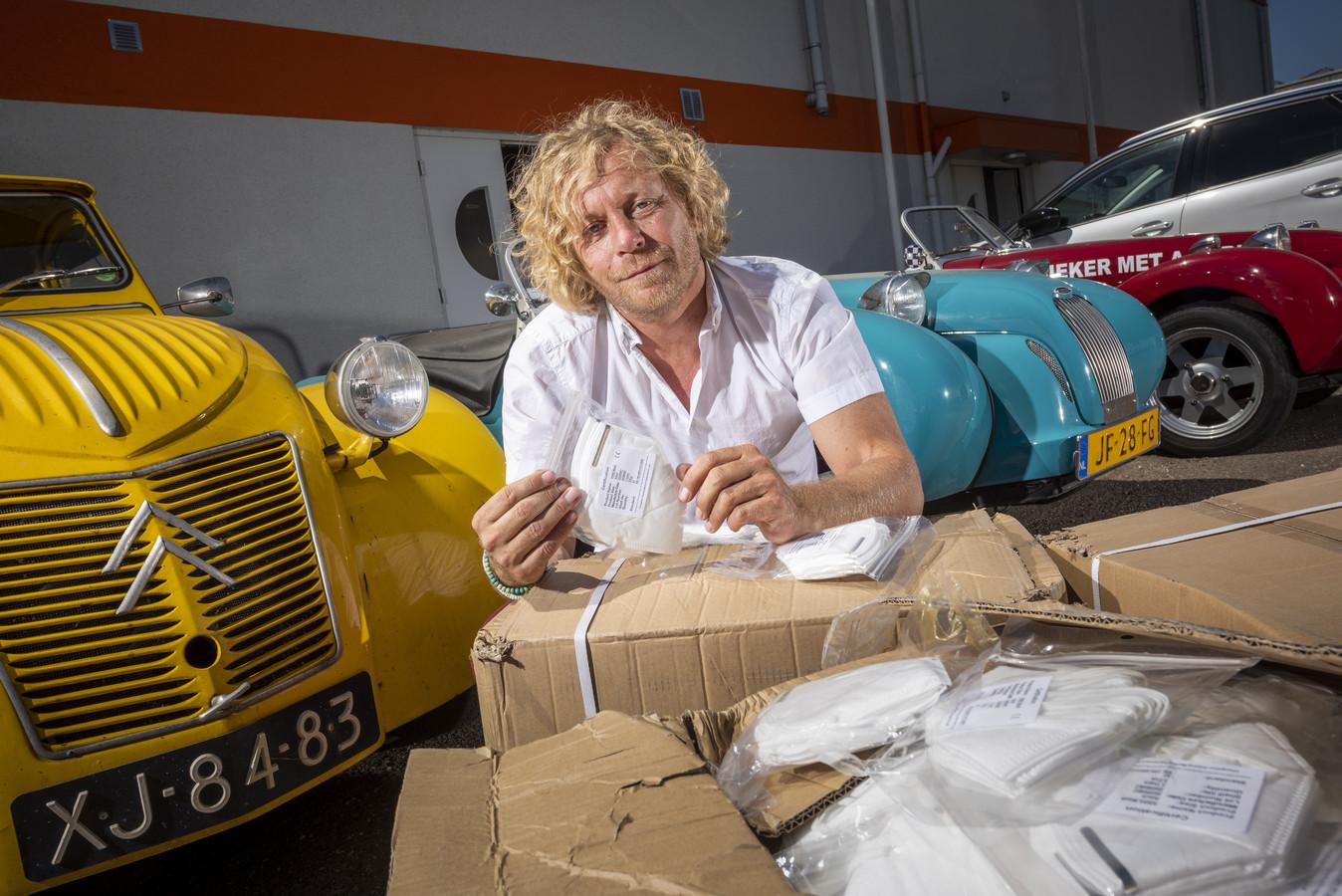 Iwan Göbel voor een paar Burtons, sportwagens op het onderstel van een lelijke Eend. Voor hem dozen vol mondkapjes, die hij het afgelopen jaar naar Nederland haalde via contacten die hij opdeed met zijn sportautofabriek in Zutphen.