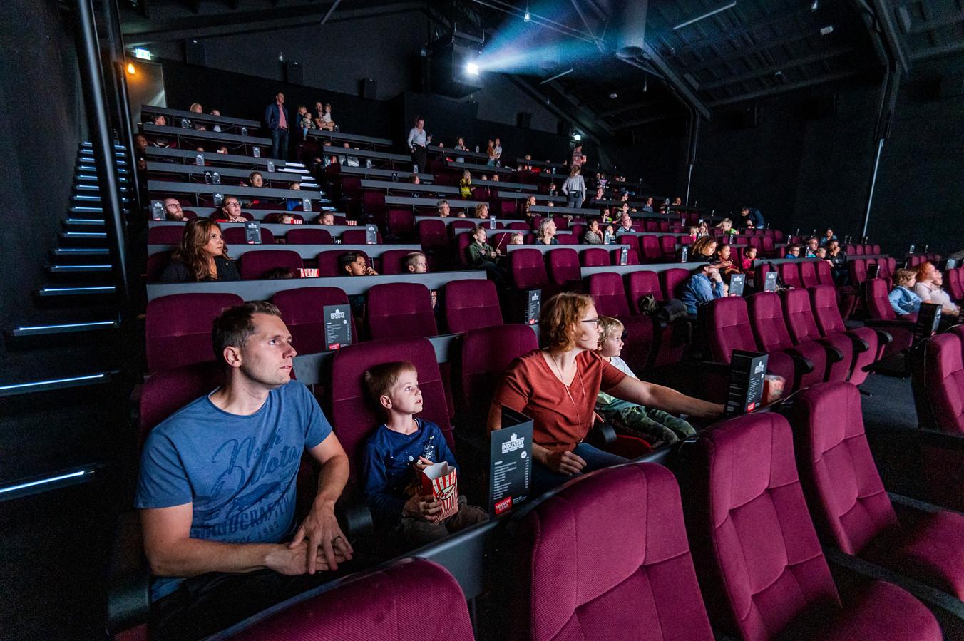 De grote bioscoopzaal stroomt vol met kinderen en hun ouders voor de eerste film na de opening.