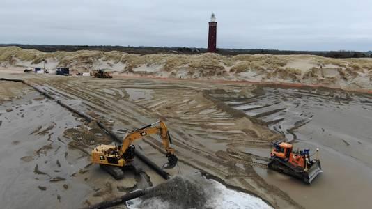Het opspuiten van zand bij het strand van Ouddorp.