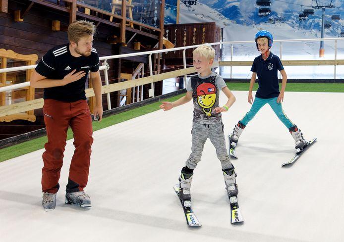 Morris (7) en Jochem (9) krijgen les van skileraar Sven Koks op de rolbaan bij Indoorski Den Bosch. Hun vader hoopt dat ze volgend jaar op wintersport mee de bergen in kunnen.