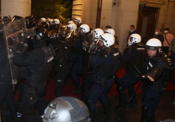 """Protesters scuffle with police in front of the National Assembly building in Belgrade, on July 7, 2020, as Serbian police fired tear gas to disperse thousands of protesters angry at the return of a weekend coronavirus curfew. - The crowds protested in the city centre over the government's handling of the crisis, with infections now spiking after Serbia shed its initial lockdown measures two months ago. Scuffles broke out between police and a group of protesters who stormed into the parliament building and police unleashed tear gas canisters to disperse the crowd. The demonstrators, who also lit flares and were seen throwing stones at police on local TV, chanted for President Aleksandar Vucic to """"Resign!"""". (Photo by OLIVER BUNIC / AFP)"""
