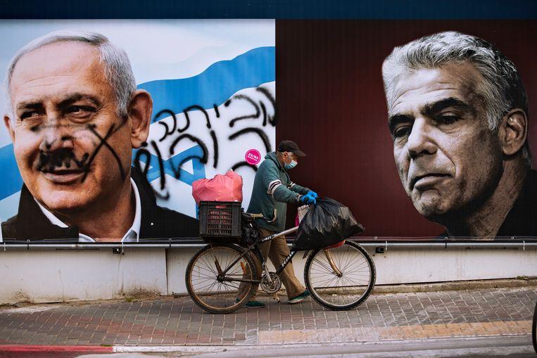 Verkiezingsposters met links premier Netanyahu, en rechts Yair Lapid. Over het gezicht van Netanyahu is de tekst 'ga naar huis' geschreven.  Beeld AP