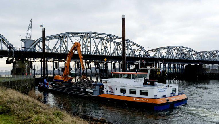 Medewerkers van Rijkswaterstaat bouwen een tijdelijke dam bij de beschadigde stuw van Grave. Met deze oplossing is scheepvaartverkeer weer mogelijk op de Maas tussen Grave en Sambeek. Beeld ANP