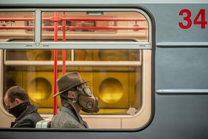 Een man met een gasmasker in de metro van Praag eerder dit jaar. Tjechië voert vandaag opnieuw de mondkapjesplicht op straat en in de auto.
