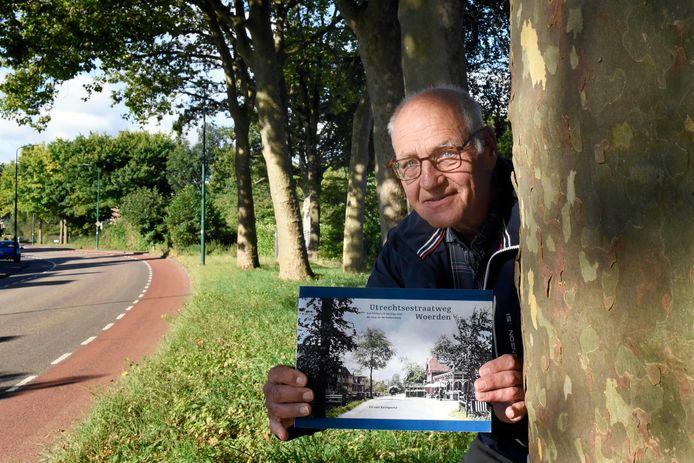 Ed van Keimpema met zijn nieuwe boek over de Utrechtsestraatweg. Hij staat bij de platanen die in zijn boek voorkomen.