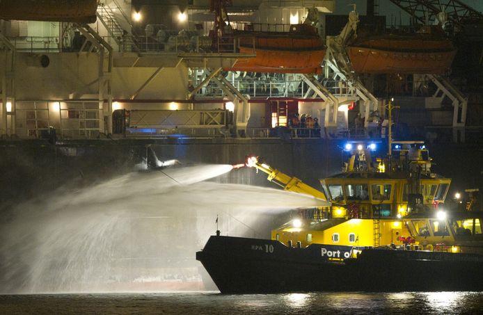 Een blusboot in de haven van Rotterdam. Op een schip, een zogeheten pijpenlegger, die in de Nieuwe Waterweg ligt woedde een grote brand. © ANP